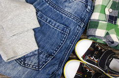 Children`s clothing set. Of sneakers, jeans and plaid shirts Royalty Free Stock Image