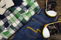 Children`s clothing set. Of sneakers, jeans and plaid shirts Stock Photos