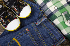 Children`s clothing set. Of sneakers, jeans and plaid shirts Royalty Free Stock Photo