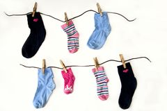 Children`s colored socks of different sizes weigh on ropes stock images