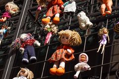 Children`s colorful soft toys hanging on strings at a market stall Stock Images