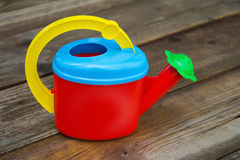 Children's colorful watering can for watering plants in the garden Stock Photo