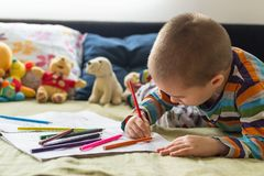 Little child boy drawing with color pencils. Children`s creativity. Boy sitting on the bed and drawing on coloring book with color pencils Royalty Free Stock Photography