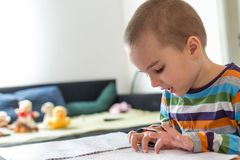 Cute boy sitting at table and playing with coloring book. Children`s creativity. Boy sitting at table and playing with coloring book Stock Photos