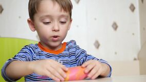 Children`s creativity. The child molds a ball of dough. Cute little boy forms from plasticine on the table. 4k stock video footage