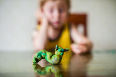 Children`s creativity. child sculpts from clay.Cute little boy moulds from plasticine on table Stock Images