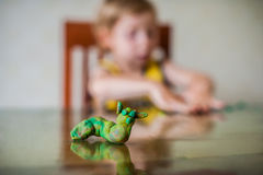 Children`s creativity. child sculpts from clay.Cute little boy moulds from plasticine on table royalty free stock photos