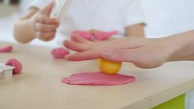 Children`s creativity. Close-up of the hands of mom and child form the shapes of the dough on the table. Cute children`s. Plasticine figurines on the table. 4k stock video