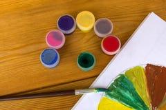 Children`s creativity. Drawing paints. 12 colors of paint. Color palette. Paints on a wooden background. Watercolor paints. artis royalty free stock photo