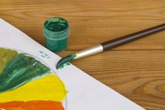 Children`s creativity. Drawing paints. Green paint. Color palette. Paints on a wooden background. Watercolor paints royalty free stock photography