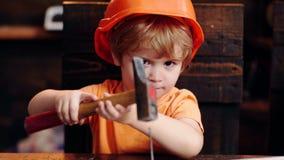 Children`s creativity engineering education - boy in workshop. Little boy in helmet clogs the nail. Little builder. Concept stock footage