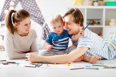 Children`s creativity. happy family mother father and   son draw. Children`s creativity. happy family mother father and baby son draw together Stock Images