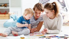 Children`s creativity. happy family mother father and   son draw. Children`s creativity. happy family mother father and baby son draw together Royalty Free Stock Image
