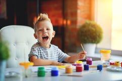 Children`s creativity. happy funny kid boy draws paints. In kindergarten stock images