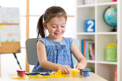 Children`s creativity. Kid sculpts from clay. Cute little girl moulds from plasticine on table. In nursery royalty free stock photo