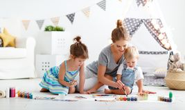 Children`s creativity. mother and children draw paints in play. Children`s creativity. mother and children draw paints in the playroom stock images