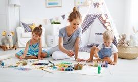 Children`s creativity. mother and children draw paints in play. Children`s creativity. mother and children draw paints in the playroom stock photos