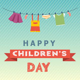 Children's Day concept. On a blue background hanging baby  clothes skirt, T-shirt, sundress, panties, socks. Below a red ribbon with the inscription Children's Stock Photos