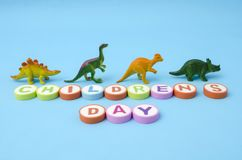 Children`s Day made from colorful letters and plastic dinosaur toys. Against blue background royalty free stock photography