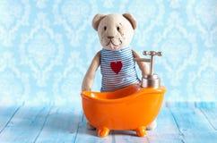 Children& x27; s de zachte stuk speelgoed teddybeer wordt gebaad in het oranje huis van de badpop Blauwe badkamers aan Het spelen Stock Foto's