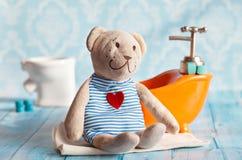 Children& x27; s de zachte stuk speelgoed teddybeer wordt gebaad in het oranje huis van de badpop Blauwe badkamers aan Het spelen Stock Afbeeldingen