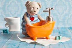 Children& x27; s de zachte stuk speelgoed teddybeer wordt gebaad in het oranje huis van de badpop Blauwe badkamers aan Het spelen Stock Afbeelding