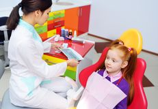 Children`s dentist examines the teeth and mouth of the child - a cute red-haired girl sitting in a dental chair stock image