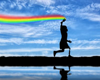 Children`s disability concept. The child has a disability with a prosthetic leg with a brush in hand, runs, and draws a rainbow in the sky near the river royalty free stock photography
