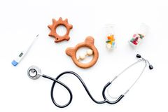 Children`s doctor concept. Stethoscope, thermometer, pills, toys on white  background top view.  Royalty Free Stock Image