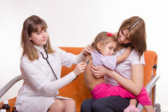 Children's doctor listening to breathing girl sitting in hands of mother Stock Photo