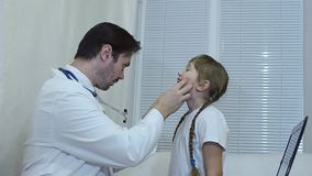 Children`s doctor looks throat of the child in the office, the doctor examines the girl in the office. stock footage