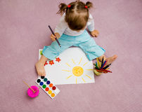 Children's drawing. The small beautiful girl draws pencils on a paper sitting on a floor Royalty Free Stock Images