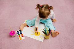 Children's drawing. The small beautiful girl draws pencils on a paper sitting on a floor Stock Image