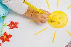 Children's drawing. The small children's hand draws a pencil the yellow sun Stock Photography
