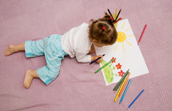 Children's drawing. The small beautiful girl draws pencils on a paper sitting on a floor Royalty Free Stock Photo