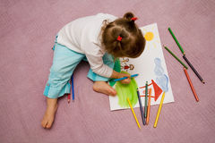 Children's drawing. The small beautiful girl draws pencils on a paper sitting on a floor Royalty Free Stock Image