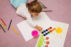Children's drawing. The small beautiful girl draws pencils on a paper sitting on a floor Stock Images