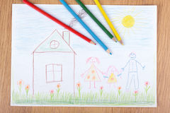 Children's drawing. Some pencils lie in children's drawing with the image of a happy family Stock Photo