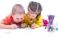 Children's drawing. Children are laying on the floor and painting pencils Stock Image