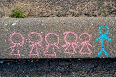 Children's drawing with chalk on the asphalt, the concept of competition and the leader. Little men. one man and many women. Children's drawing with chalk on royalty free stock photo