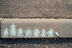 Children's drawing with chalk on the asphalt, the concept of competition and the leader. Small Christmas trees and one big one.  royalty free stock image