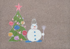 Children's drawing with chalk of snowman near Christmas tree Royalty Free Stock Photography