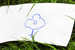 Children's drawing a flower. On the grass Stock Photos