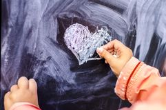 Children`s drawing heart is white chalk on a black board. Valentine day is a concept photo royalty free stock photo