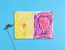 Children's drawing and mustache on blue background. Father's Day concept. Flat lay. Top view Royalty Free Stock Images