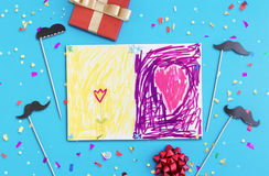 Children`s drawing, mustache, confetti and red gift box. On blue background. Father`s Day concept. Flat lay. Top view Stock Image
