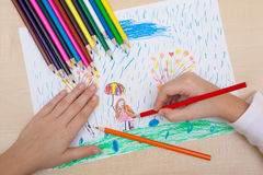 Children`s drawing pencils. The child draws a pencil drawing of a girl with an umbrella in the rain Stock Image