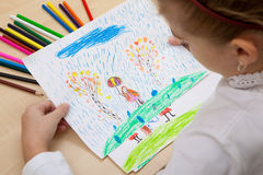 Children`s drawing pencils. The child looks pencils drawing a girl with an umbrella in the rain. Autumn weather Royalty Free Stock Images