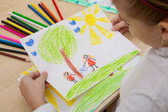 Children`s drawing pencils. The child looks drawing pencils picture of the peace Royalty Free Stock Photos