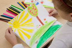 Children`s drawing pencils. Girl watching a children`s pencil drawing sun, summer, nature Stock Photo